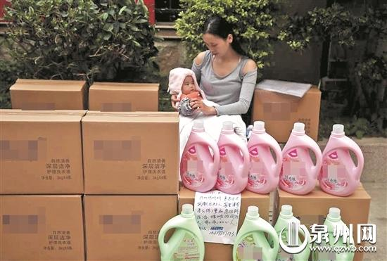 为了养家,张婷婷抱着孩子摆地摊。
