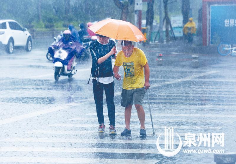 看到大叔行走吃力,小伙边撑伞边搀扶着他走。